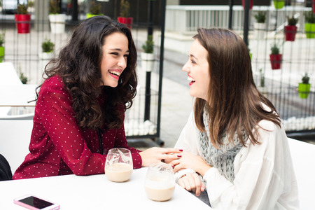 two people meeting: Young cute women laughing while having a coffee outdoors Stock Photo