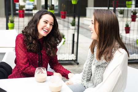 Young cute women laughing while having a coffee outdoors 스톡 콘텐츠