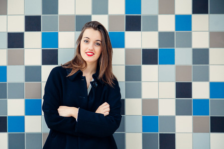 Attractive young business woman or student with arms crossed smiling against a blue mosaic wall