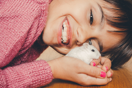 russian hamster: Close up of a happy girl hugging her hamster lovingly