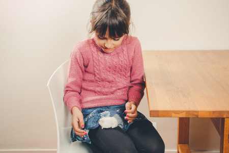 russian hamster: Cute girl in pink playing with her white hamster at home