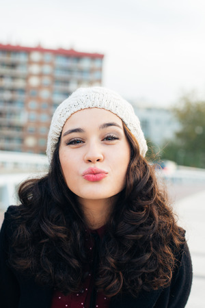 close up eyes: Urban girl with woolen cap kissing to camera in the city