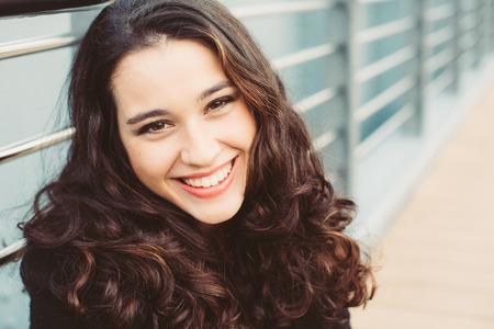 chicas sonriendo: Retrato de una hermosa mujer morena con el pelo ondulado y hermosa sonrisa Foto de archivo