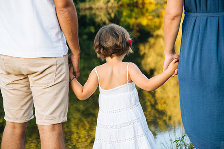 Young family holding hands on the shores of a river. Back view. Stock Photo