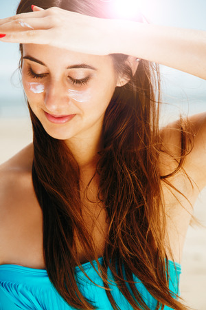 sun protection: Young beautiful woman in bikini with sun cream in cheeks protecting from the sun with hand as a sun visor in the beach. Skin and hair protection concept.