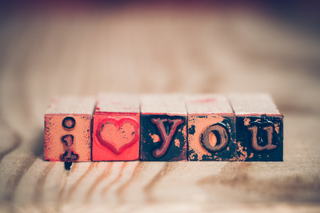 letter blocks: I love you message with used rubber stamp letter blocks on wooden table