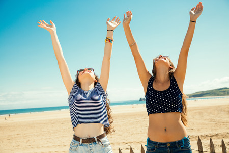 teen bikini: Funny girl friends with arms outstretched greeting the sun on the beach