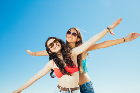 pretending: Happy best friends in bikini pretending flying with arms outstretched against a blue sky