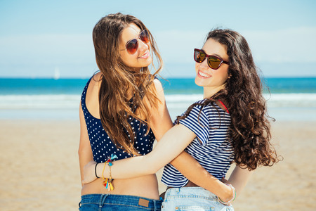 Happy girl friends hugging on the beach