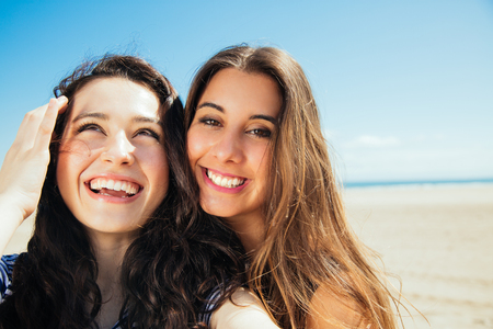 teen bikini: Funny female friends on vacation taking selfies on the beach with a smart phone
