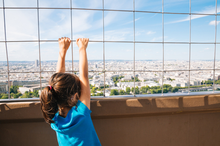 second floor: Little girl looking the cityscape of Paris from the second floor of the Eiffel Tower holding the protection grille