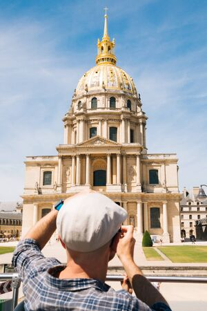 Tourist man with cap taking pictures of the church of les Invalides in Paris from a touristic bus. Focus on the church