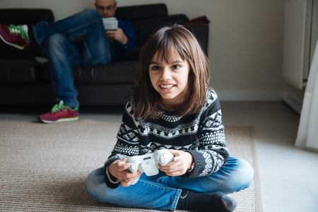 Little girl playing video games while her father is reading a book at home