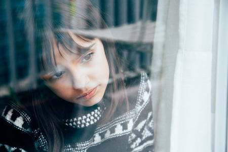 Sad little girl looking through the window with reflections on her face