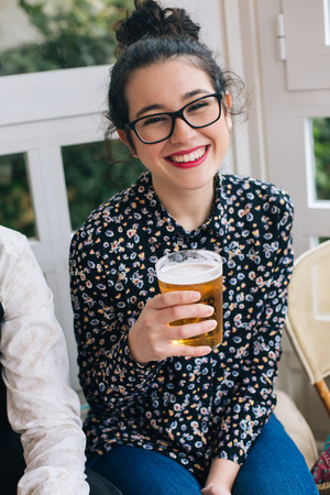 topknot: Portrait of a young cute modern woman drinking beer in a bar with friends