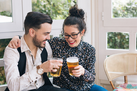 two couples: Young modern couple toasting with beer