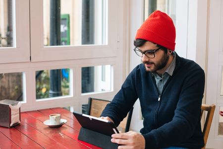 one man: Young attractive man with glasses and woolen cap using a digital tablet in a contemporary cafe Stock Photo