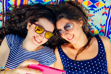 mirrored: Young happy girl friends lying on the beach taking a self portrait wiht a smart phone