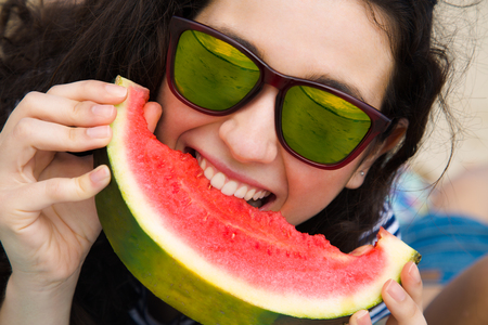 mirrored: Funny portrait of a young woman with sunglasses eating watermelon on the beach Stock Photo
