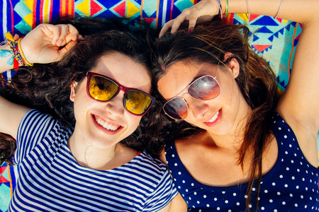 Colorful portrait of young happy girl friends with sun glasses lying on the beach