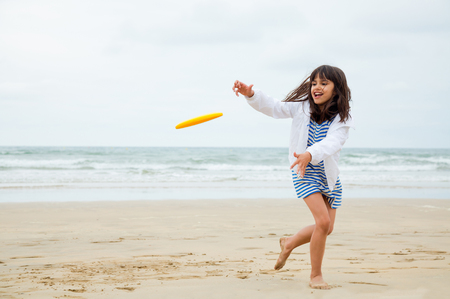 Girl running to catch the flying frisbee disc on the beach in a cloudy day Banque d'images