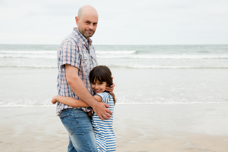 cuddled: Father and daughter embracing on the beach Stock Photo