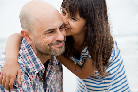 cuddled: Cute daughter kissing her father and laughing Stock Photo