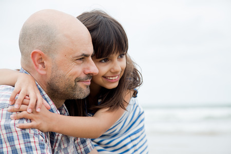 cuddled: Father and daughter embracing looking out of camera on the beach Stock Photo