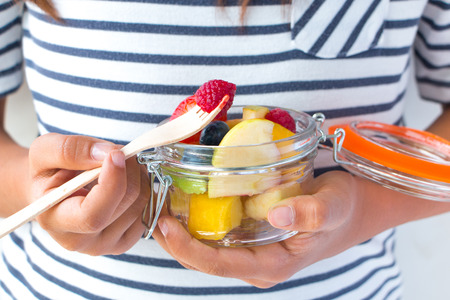 healthy snack: Little girl hands eating a fruit salad on a jar. Healthy snack for children concept Stock Photo