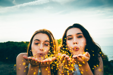 Funny female friends blowing golden glitter over a cliff at dusk Stock Photo