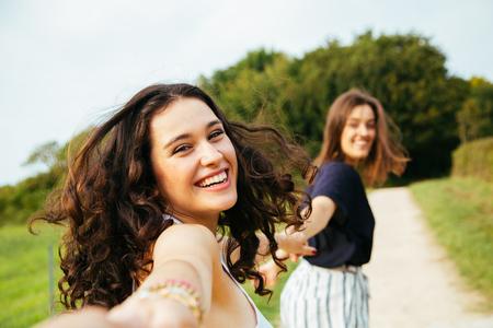Due ragazze felici in esecuzione in natura si tengono per mano. Point Of View Shot. Archivio Fotografico