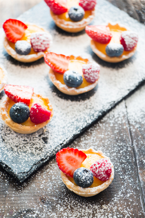 Small tarts of cream and fresh berries with icing sugar