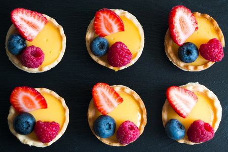 samll: Little pastry tarts filled with cream and fresh berries Stock Photo