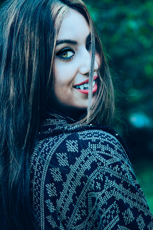 Beautiful vampire woman turning head back looking at you