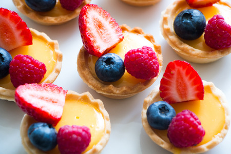 Little pastry tarts filled with cream and fresh berries Stock Photo