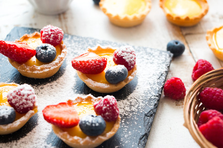 Preparing small pastry tartlets filled with vainila cream and fresh berries in a rustic white wooden table