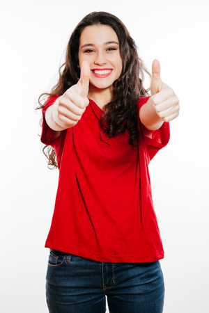 excited woman: Young positive brunette woman showing thumbs up smiling. Isolated on white