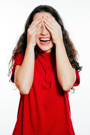 covering eyes: Portrait of surprised and laughing young woman covering eyes with hands. Isolated on white