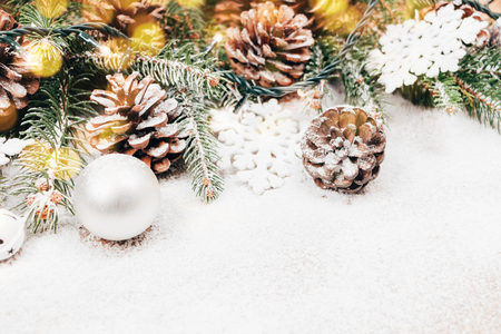 pinecones: Snowy Christmas background with fir, pinecones, tree ornaments and lights