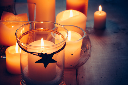 Christmas candles with a tied star on a wooden background at nigth