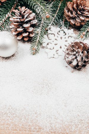 pinecones: Snowy Christmas background with fir, pinecones and tree ornaments