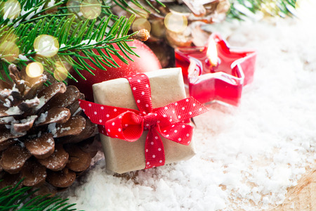 red polka dots: Caja de regalo de Navidad con un rojo lunares arco y adornos, abeto y pino conos en la nieve