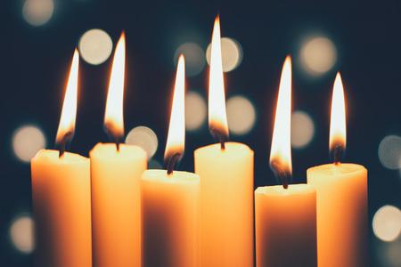 Gruppe von dünnen Kerzen brennen und Bokeh der Weihnachtsbeleuchtung im Hintergrund