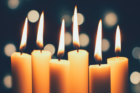 Group of thin candles burning and bokeh of Christmas lights at the background