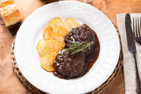 carne roja: carrillada de cerdo guisadas con vino tinto y patatas fritas con un resorte de romero Foto de archivo
