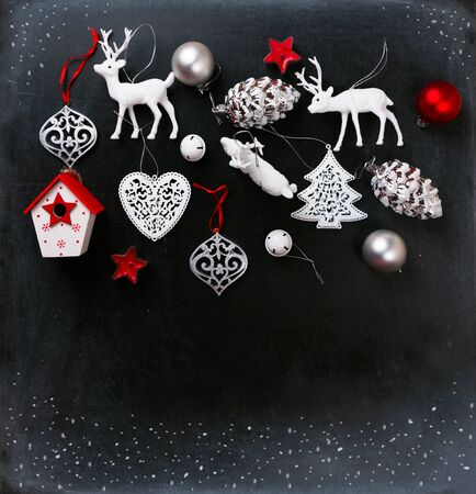 Christmas ornaments in white, silver and red on a blackboard background with drawn snow. Copy space. Stock Photo