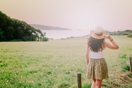basque woman: Rear view of a young woman with pamela contemplating the landscape of the countryside and the coast in a sunny day. Filter effect added. Stock Photo