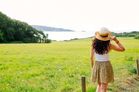 basque woman: Rear view of a young woman with pamela contemplating the landscape of the countryside and the coast in a sunny day Stock Photo