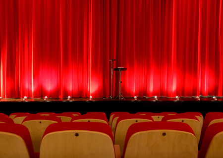 Stage with red curtain and empty seats of a theater waiting for the show Stock Photo