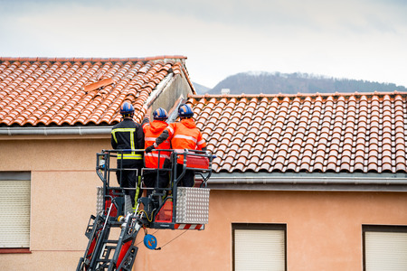 Firemen up in a crane removing detached tiles from a roof in a windy and rainy day